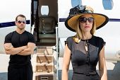 stock photo of bodyguard  - Beautiful woman wearing sunhat with bodyguard and private jet in background - JPG