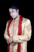 image of sherwani  - A portrait of a handsome Indian groom in a traditional attire on black studio background - JPG