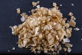 picture of anglesey  - Pile of welsh oak smoked sea salt flakes on dark slate background - JPG