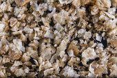 stock photo of anglesey  - Pile of welsh oak smoked sea salt flakes on dark slate background - JPG