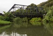 image of girder  - View of the old steel girder bridge over Hanalei river from a canoe floating down the wide stream under the road bridge - JPG