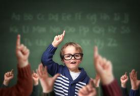 image of child development  - School child with hand raised in the classroom in front of a blackboard with other children concept for teacher - JPG