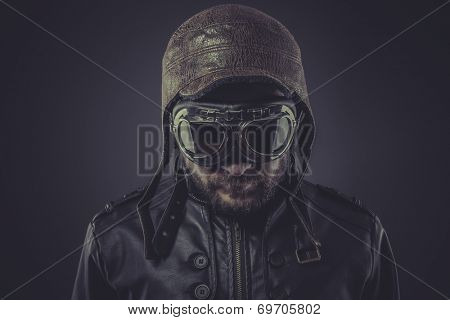 ww2 pilot dressed in vintage style leather cap and goggles