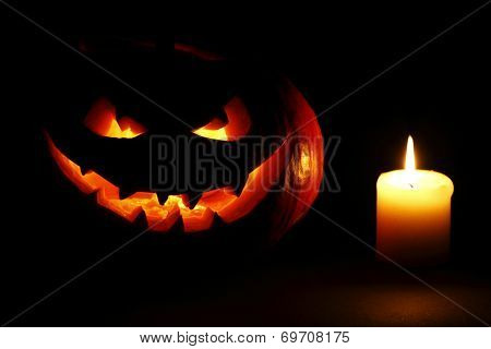 Halloween carved pumpkin and candle on black background