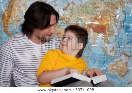 Dad And Son Reading A Book On A Map Of The World