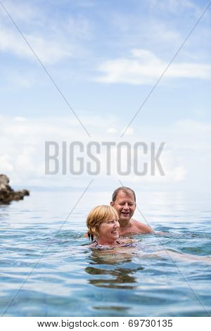 Senior couple enjoying the retirement on a seacost, having a swim in the sea, laughing togther, staying active and positive