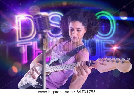 Pretty girl playing guitar against digitally generated colourful discotheque text