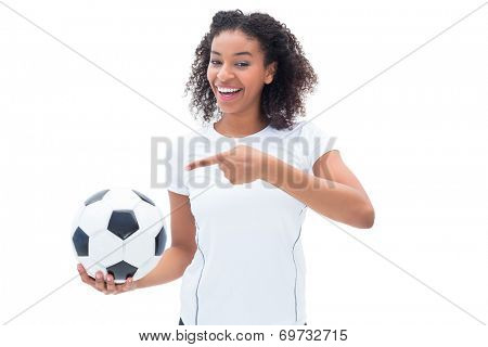 Pretty football fan in white holding ball and pointing to it on white background