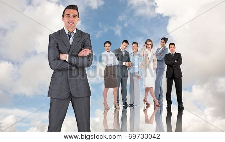 Businessman in grey suit smiling at camera against blue sky with white clouds