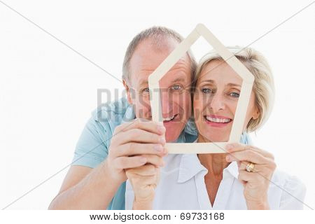 Happy older couple holding house shape on white background