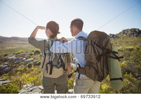 Hiking couple looking out over country terrain on a sunny day