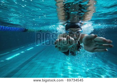 Athletic swimmer training on her own in the swimming pool at the leisure centre
