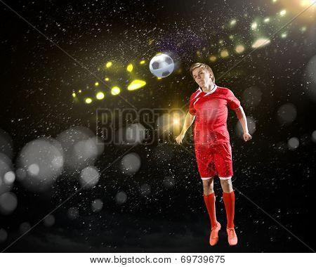 Young football player on stadium kicking ball with head in jump