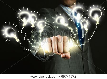 Close up of businessman hand holding light bulbs in fist