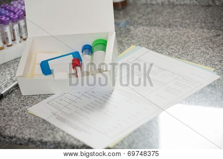 Specimen bottles in box with documents on counter in lab