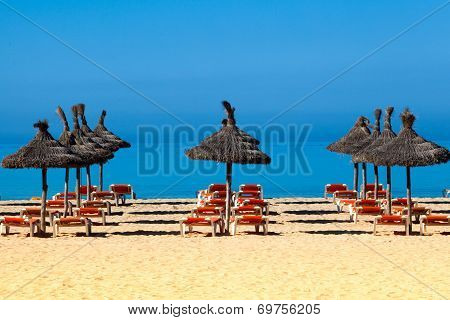 Tropical Beach Scenery With Parasol And Deck Chairs.  Umbrella And Deck Chairs
