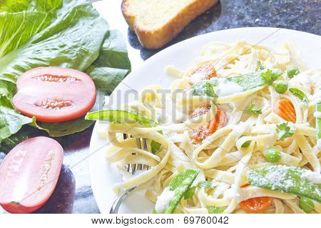 Fettuccini Alfredo with snap peas and carrots
