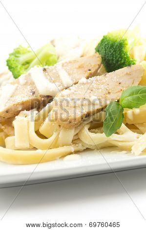 Chicken Fettuccini alfredo with fresh basil leaves and steamed fresh broccoli delicious