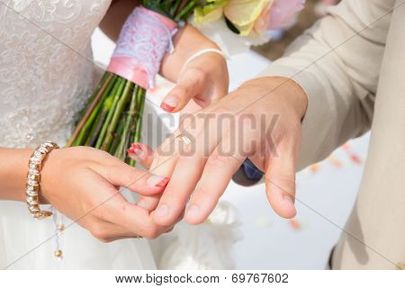 Close up bride put the wedding ring on groom
