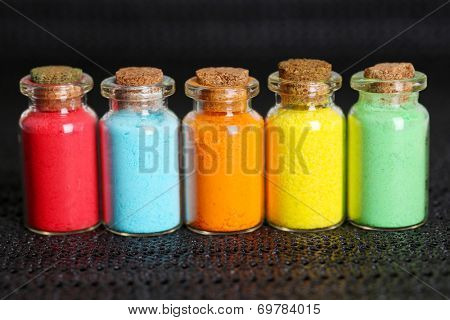 Bottles with colorful dry pigments on dark background
