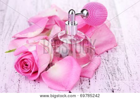 Perfume bottle with roses petals on table close-up
