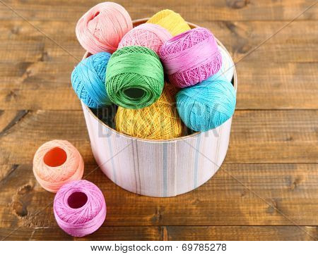 Clews for hook knitting in a box on wooden background