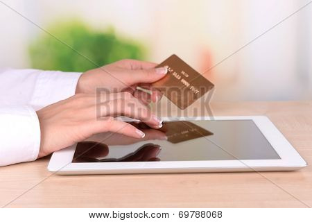 Female hands holding credit card and computer tablet on table on bright background