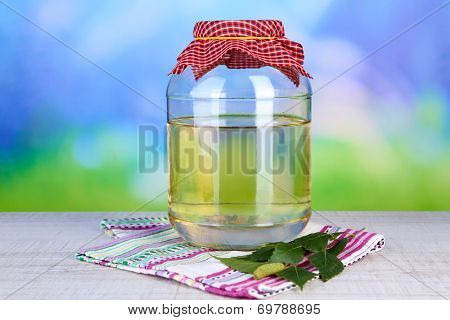 Large flagon of fresh birch sap on a table on nature background