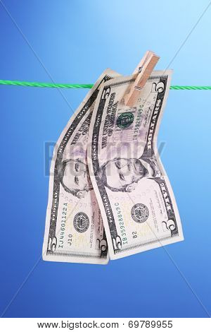 Dollar bills hanging on rope attached with clothes pins. Money-laundering concept. On color background.