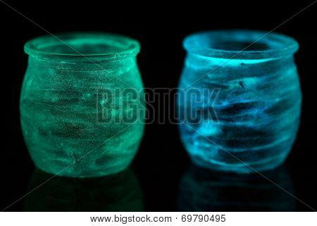 Candlesticks painted fluorescent paint isolated on black