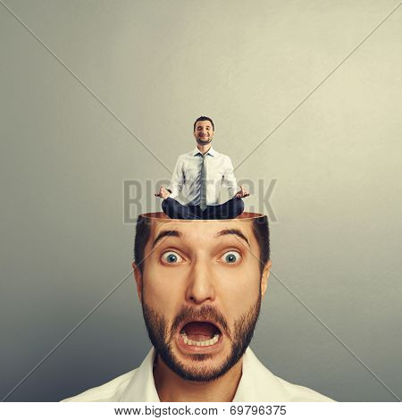 stressed businessman with open head. young calm businessman sitting in yoga asana and smiling in the man's head. photo over grey background