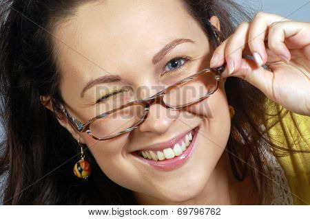 Portrait About Smiling And Winking Woman In Glasses