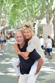 pic of tree lined street  - Playful mature couple having a piggy back ride in a tree lined urban street stopping top smile at the camera as the husband carries his wife across the street - JPG