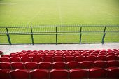 stock photo of bleachers  - Red bleachers looking down on football pitch on a clear day - JPG
