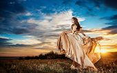 image of leaving  - Fashionable beautiful young woman in nude colored long dress leaving - JPG