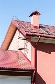 foto of red roof tile  - House with rain gutter drainpipes and red tiled roof - JPG