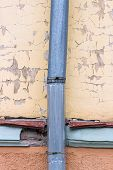 stock photo of downspouts  - Old galvanized downspout against weathered plaster wall - JPG