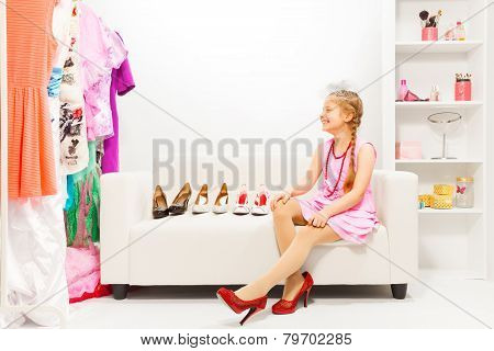 Beautiful girl sits on sofa choosing right shoes