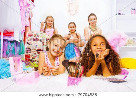 Beautiful pretty girls apply make-up on carpet