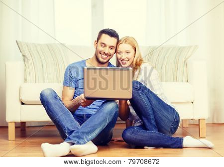love, family, technology, internet and happiness concept - smiling happy couple with laptop computer sitting on the floor at home