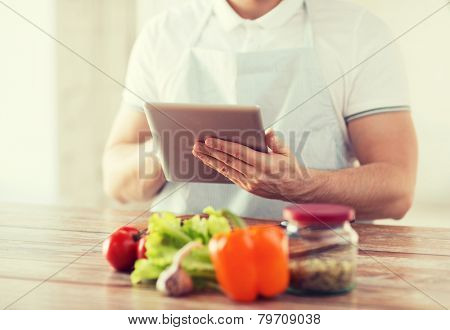 cooking, technology and home concept - closeup of man reading recipe from tablet pc computer