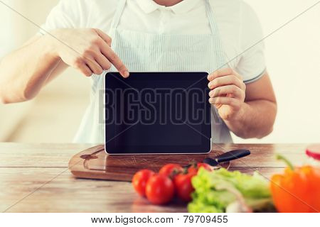 cooking, technology, advertising and home concept - close up of male hands holding tablet pc with blank black screen and pointing to it