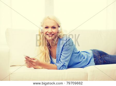 home, technology and internet concept - smiling woman with smartphone and headphones lying on couch at home
