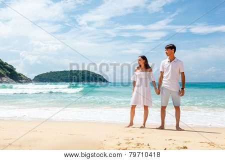 couple on beach standing and looking far away