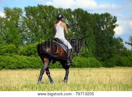 Young lady in equestrian uniform on German pony comes back