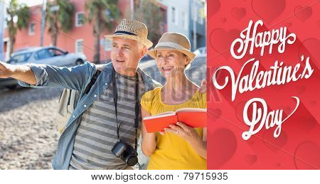 Happy tourist couple using guide book in the city against cute valentines message