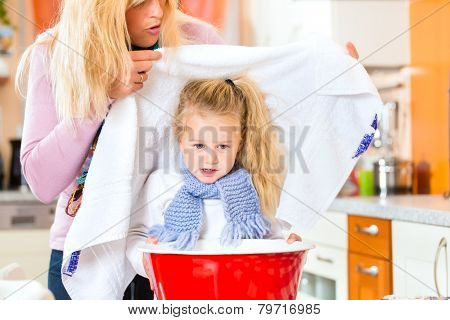 Mother care for sick child with vapor-bath at domestic kitchen