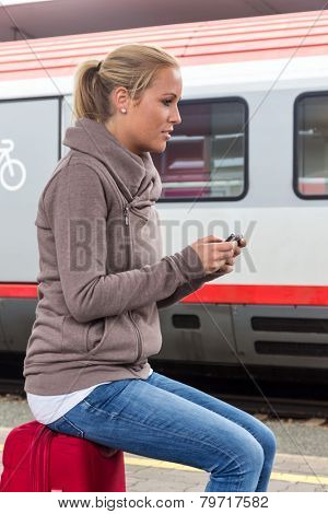 a young woman waiting for a train and writes with her cell phone a sms