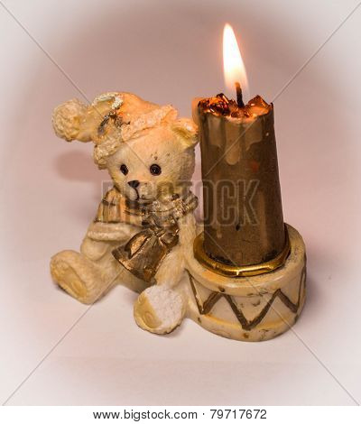 An inflamed candle with ceramic bear