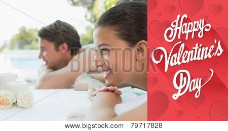 Couple lying on massage table at spa center against cute valentines message